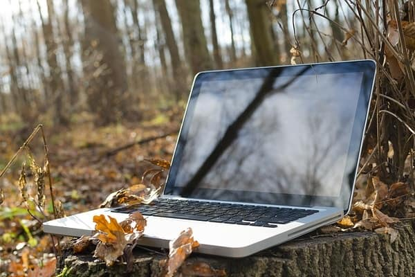 Laptop in the woods signifying being able to work with a semi-retire plan