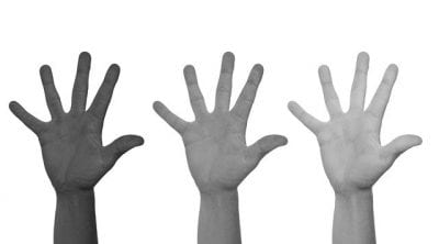 hands of difference races in the air to address racism
