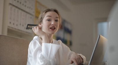 young woman with credit card paying online not demonstrating money advice for kids
